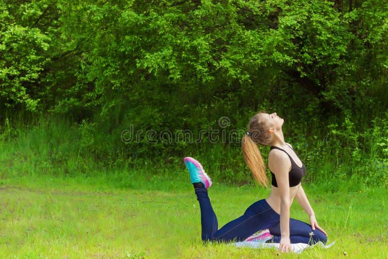 La bella ragazza è impegnata negli sport, l'yoga, forma fisica sulla spiaggia dal fiume un giorno di estate soleggiato immagine stock libera da diritti