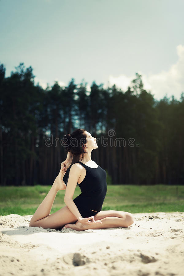 La bella ragazza è impegnata nell'yoga nella foresta sulla sabbia immagini stock