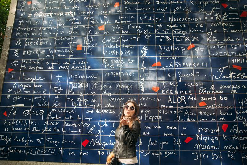 La bella ragazza è walkin a Parigi vicino alla basilica la parete dell'amore immagine stock