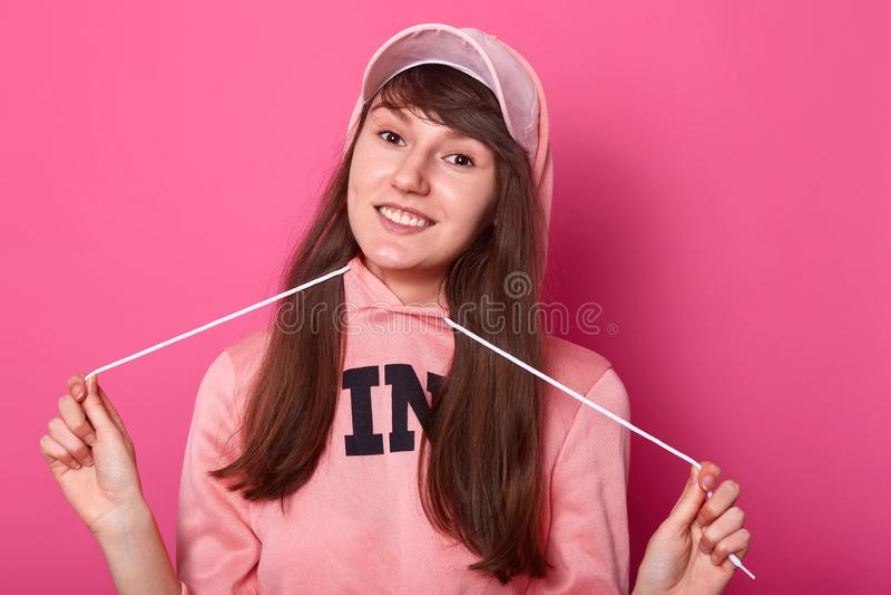 La bella ragazza affascinante indossa la maglia con cappuccio ed il cappuccio rosa La giovane signora ha i capelli lunghi scuri,  fotografia stock