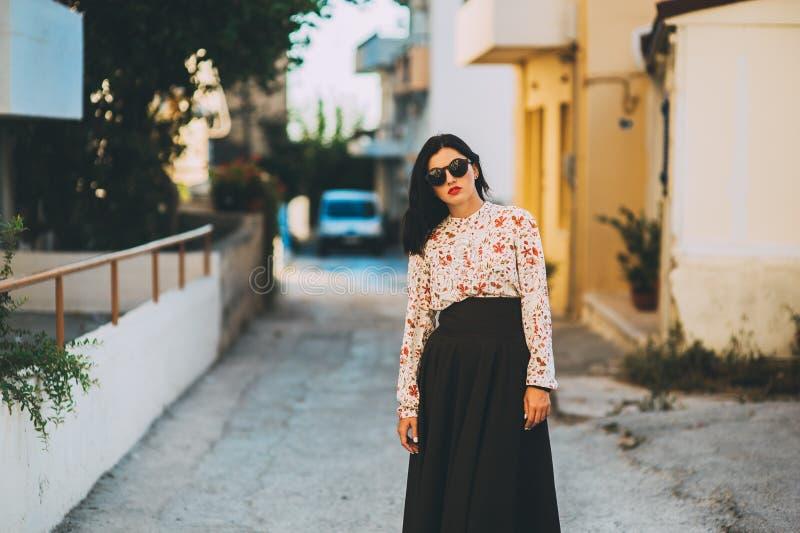 La bella ragazza alla moda cammina intorno alla città fotografia stock libera da diritti