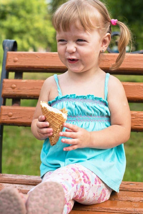 La bella ragazza allegra sorridente mangia il gelato sul banco nella t immagini stock libere da diritti