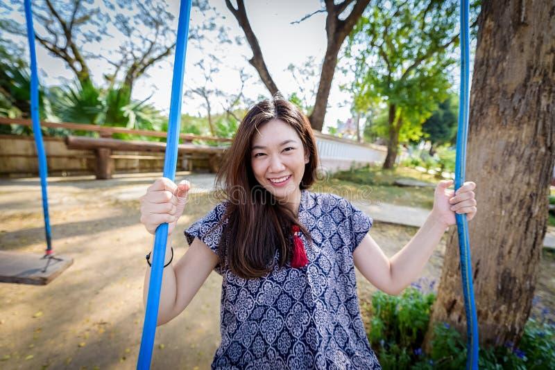 La bella ragazza asiatica ha gioco dell'oscillazione con il fondo della natura nel morming alla provincia di Nan, Tailandia fotografia stock libera da diritti