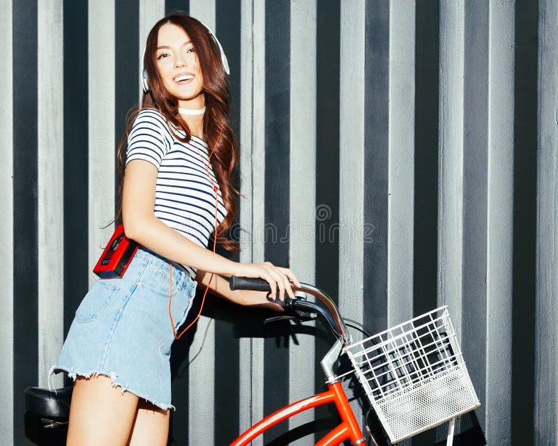 La bella ragazza asiatica stupefacente in un'attrezzatura dell'estate che posa e gode della musica Cuffie e giranastri d'annata r fotografia stock