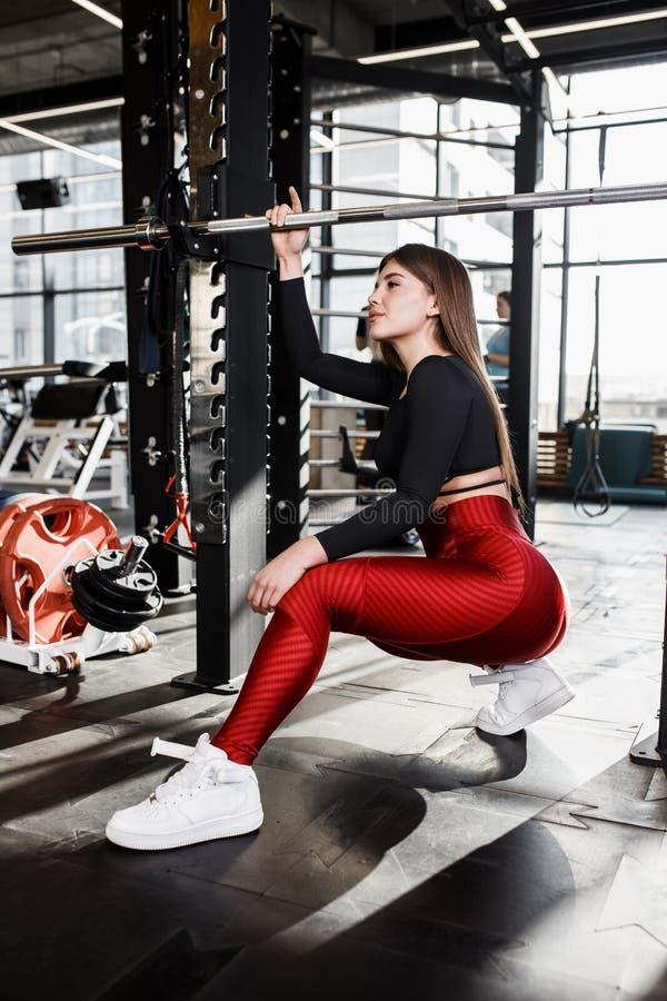 La bella ragazza atletica in vestiti luminosi alla moda di sport fa le pose accanto alla barra orizzontale nella palestra moderna fotografia stock libera da diritti