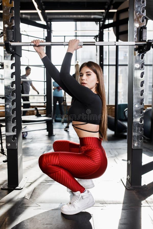 La bella ragazza atletica in vestiti luminosi alla moda di sport fa le pose accanto alla barra orizzontale nella palestra moderna immagine stock libera da diritti