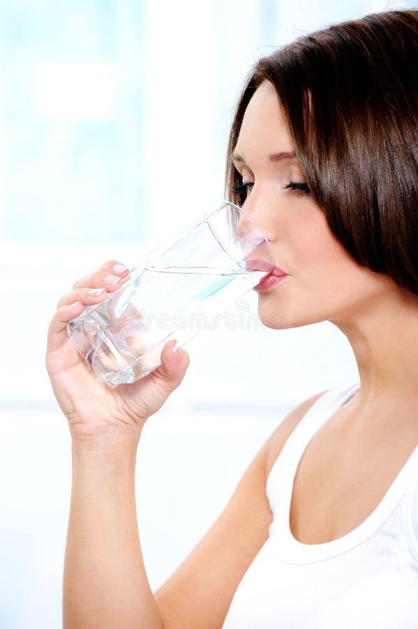 La bella ragazza beve l'acqua pura da un vetro fotografia stock