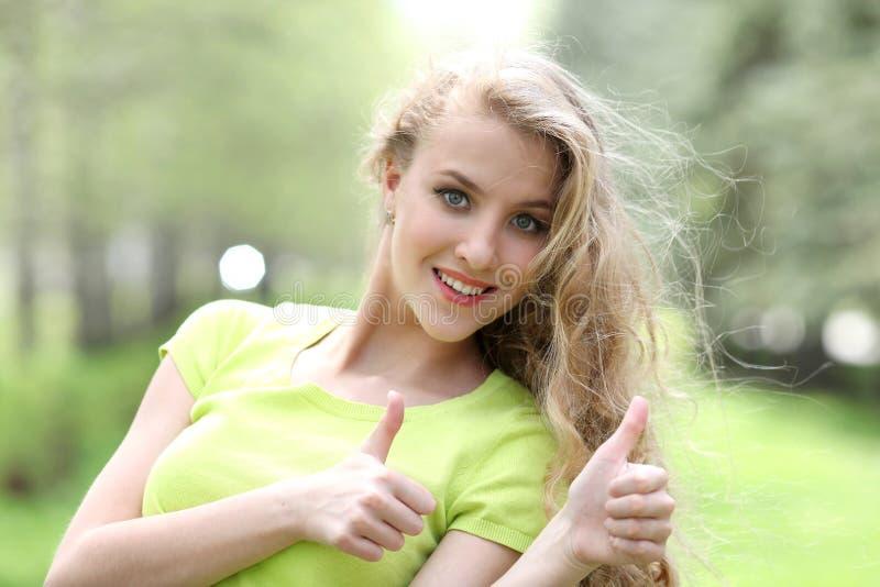 La bella ragazza bianca mostra il pollice su sulla natura nel parco immagini stock libere da diritti