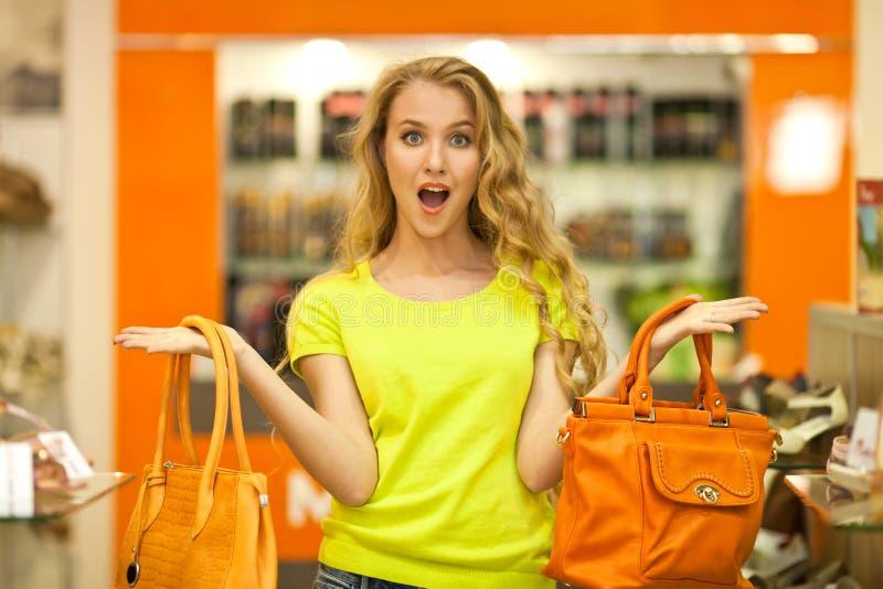 La bella ragazza bianca sceglie le borse di cuoio nel deposito Pubblicità della borsa immagini stock