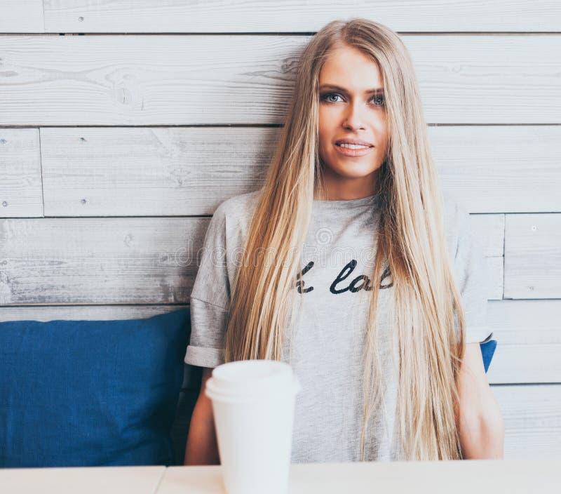 La bella ragazza bionda alla moda con capelli lunghi sta riposando in un caffè con una tazza di caffè Fondo di legno Instagram immagine stock libera da diritti