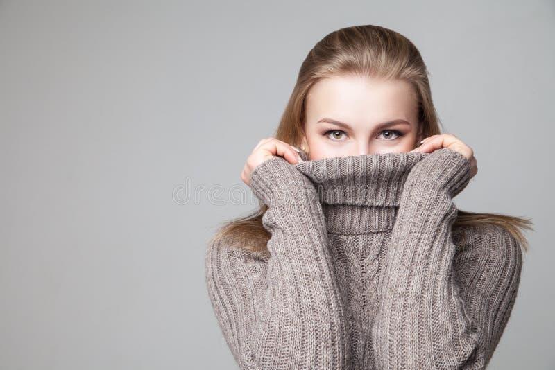 La bella ragazza bionda porta il pullover dell'inverno fotografia stock