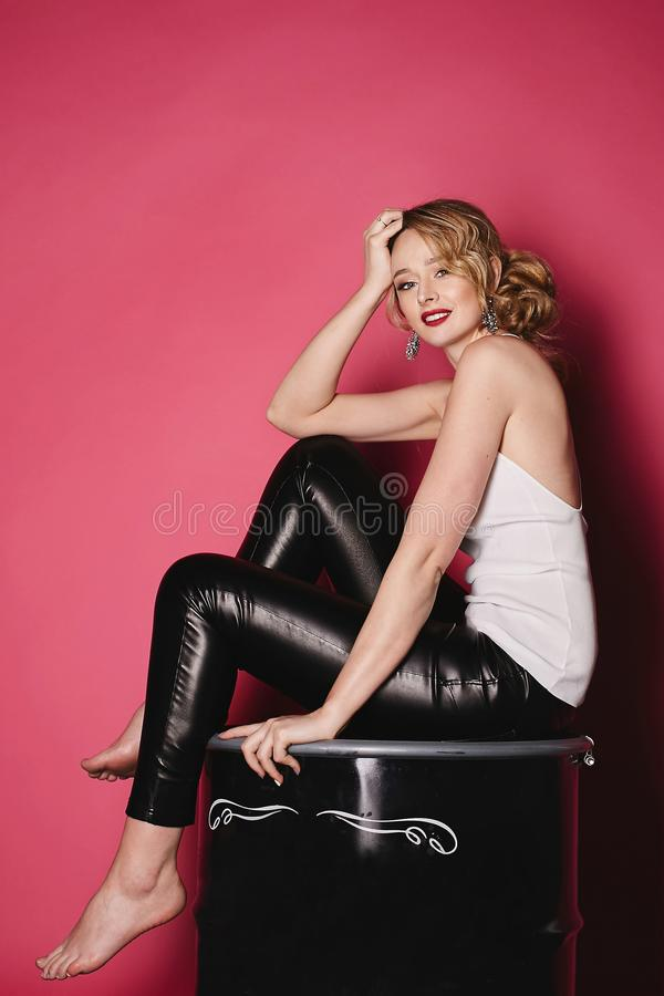 La bella, ragazza bionda sexy ed alla moda con le labbra rosse in maglietta bianca e ghette nere si siede su un barilotto nero a  fotografia stock