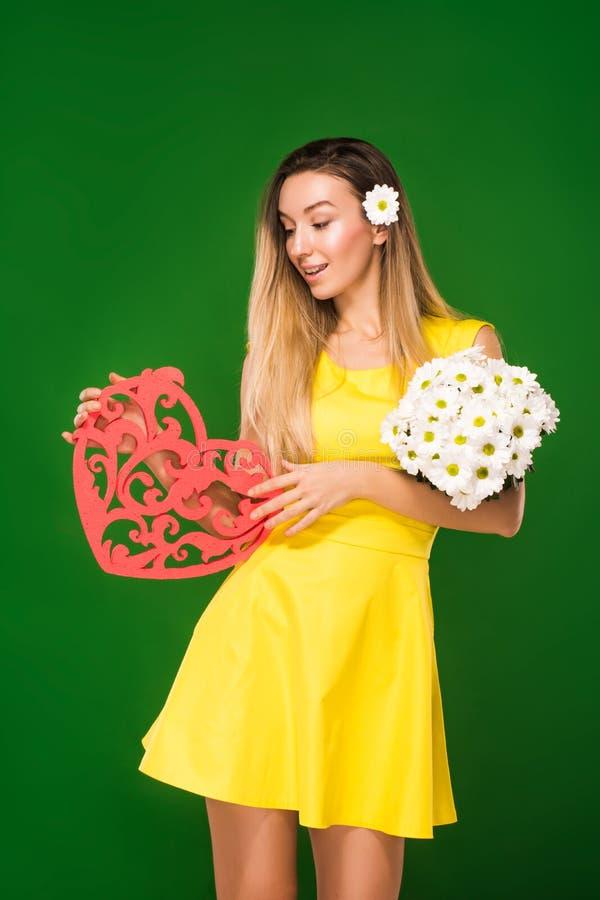 La bella ragazza bionda in un vestito giallo tiene un cuore in sue mani e un mazzo delle camomille immagine stock libera da diritti