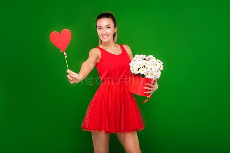 La bella ragazza bionda in un vestito rosso tiene un cuore in sue mani e un mazzo delle camomille immagini stock libere da diritti