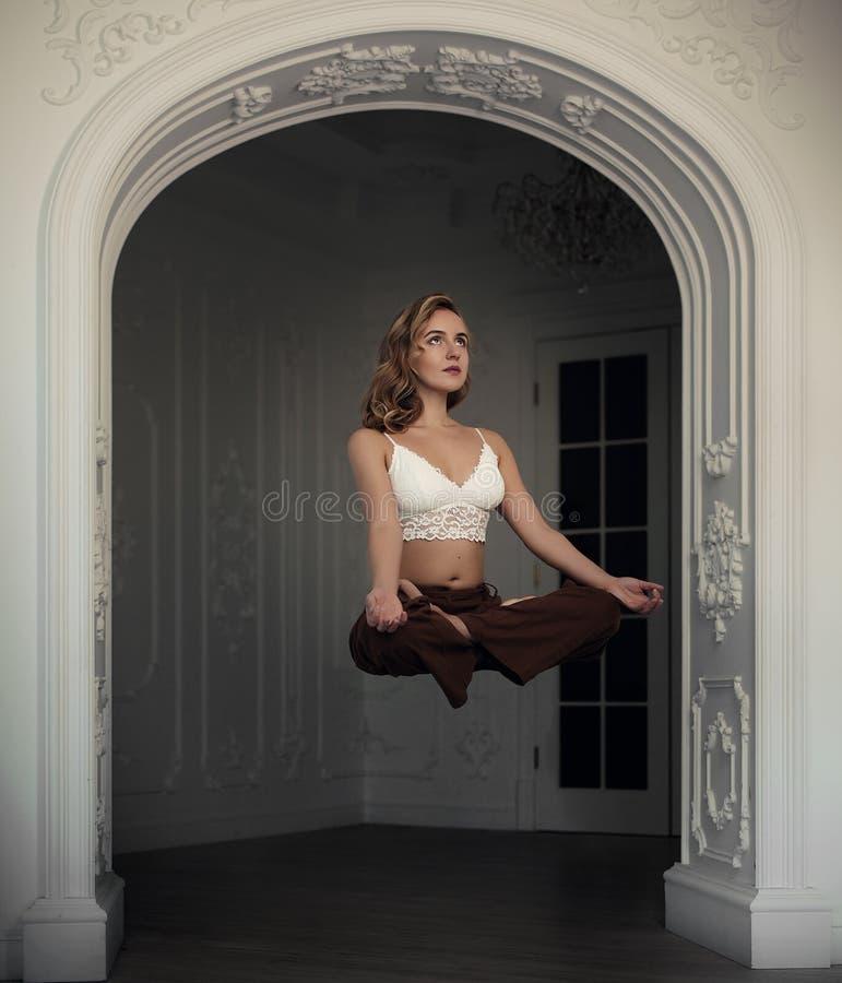 La bella ragazza bionda vola nella posizione di loto nell'interno bianco con l'arco magia di levitazione Posa di yoga fotografia stock