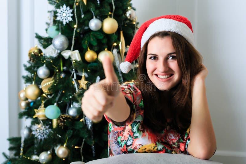 La bella ragazza in cappello di Natale che mostra i pollici aumenta l'APPROVAZIONE del segno fotografia stock
