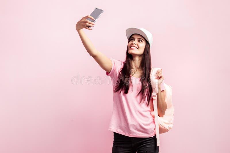 La bella ragazza in cappuccio bianco e con uno zaino sulle sue spalle vestite in maglietta rosa e jeans neri sta facendo il selfi fotografie stock