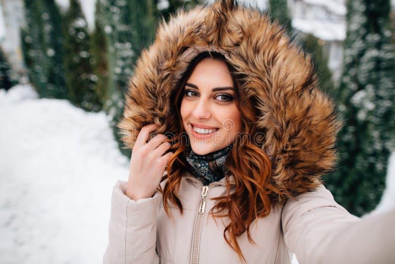 La bella ragazza in cappuccio della pelliccia prende il selfie nel giorno di inverno nevoso fotografia stock libera da diritti