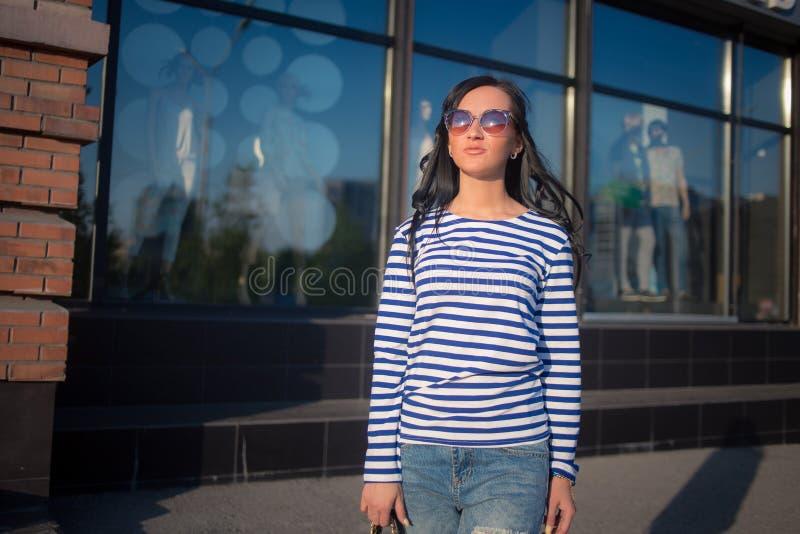 La bella ragazza castana cammina attraverso la città fotografie stock libere da diritti