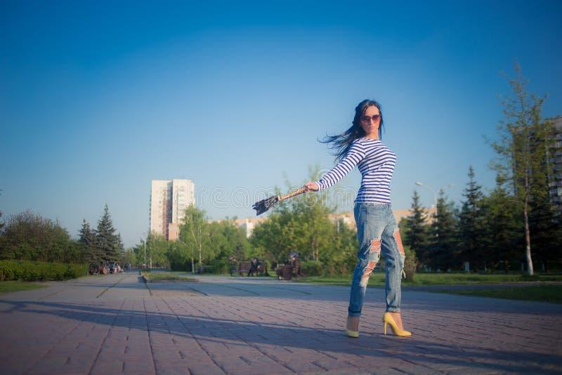 La bella ragazza castana cammina attraverso la città fotografia stock libera da diritti