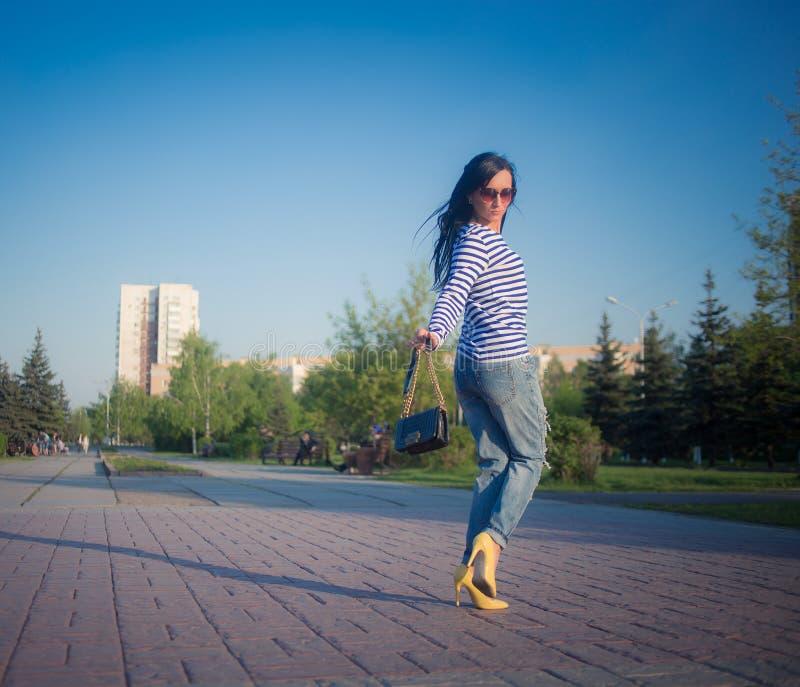 La bella ragazza castana cammina attraverso la città fotografia stock
