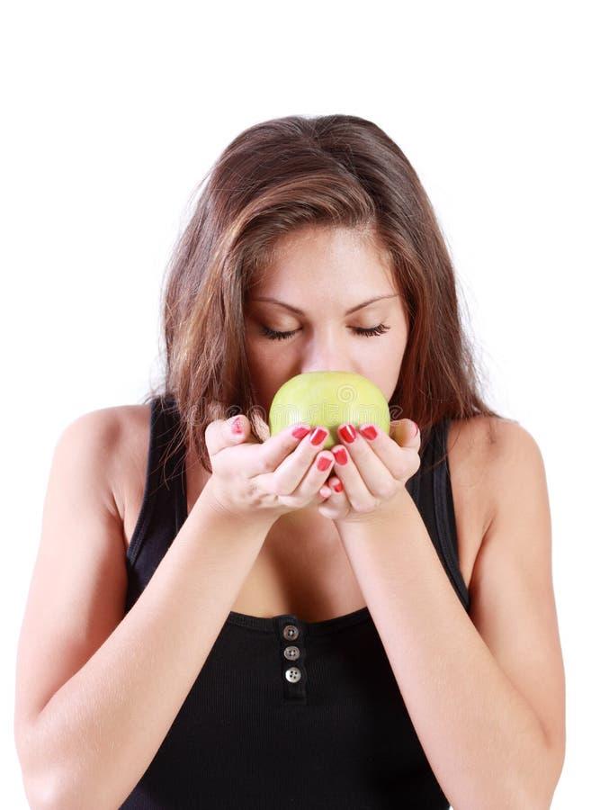 La bella ragazza castana con gli occhi chiusi fiuta la mela verde fotografie stock