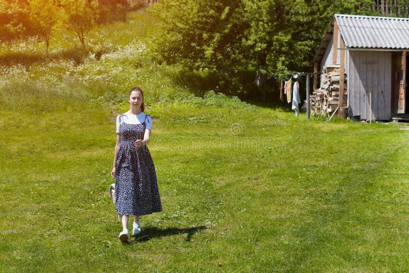 La bella ragazza castana in un vestito cammina attraverso un campo verde sui precedenti delle costruzioni del villaggio immagine stock libera da diritti