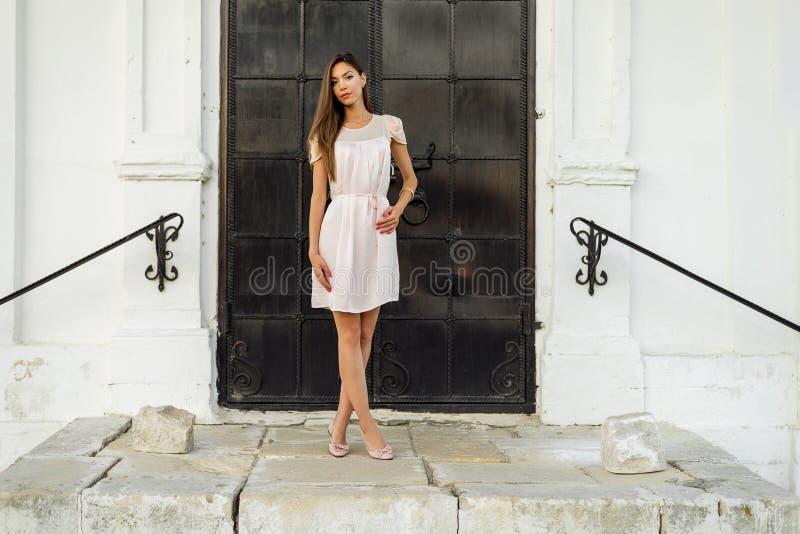 La bella ragazza castana in una porta nera del metallo sulle scale posa Stile di modo Donna abbronzata in vestito rosa all'aperto fotografia stock