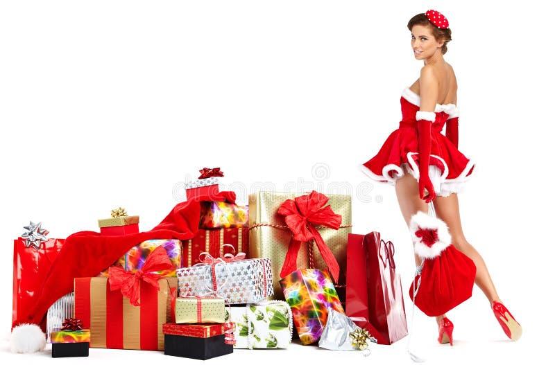 La bella ragazza che indossa il Babbo Natale copre con natale g fotografia stock