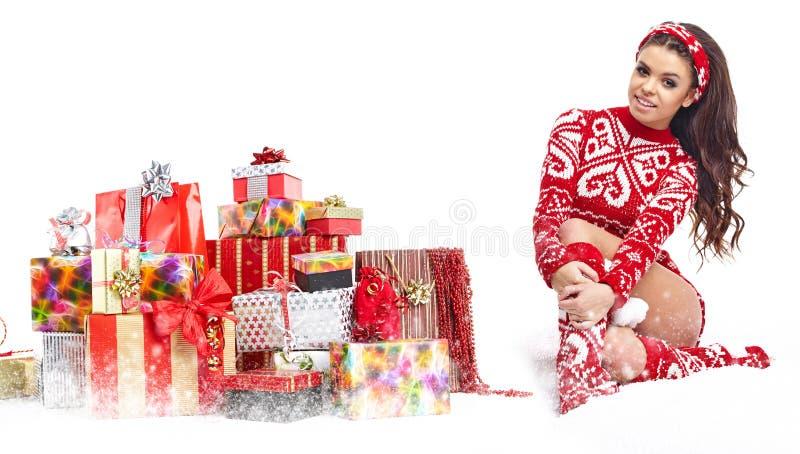 La bella ragazza che indossa il Babbo Natale copre con natale g immagini stock