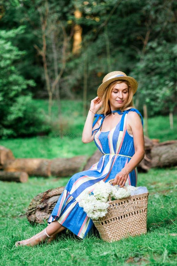 La bella ragazza che portano il vestito blu ed il cappello raccolgono la merce nel carrello dei fiori nel legno immagine stock