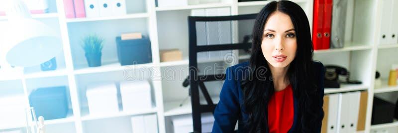La bella ragazza compila i documenti, sedentesi nell'ufficio alla tavola immagini stock libere da diritti