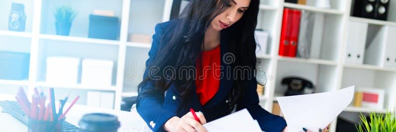 La bella ragazza compila i documenti, sedentesi nell'ufficio alla tavola fotografia stock