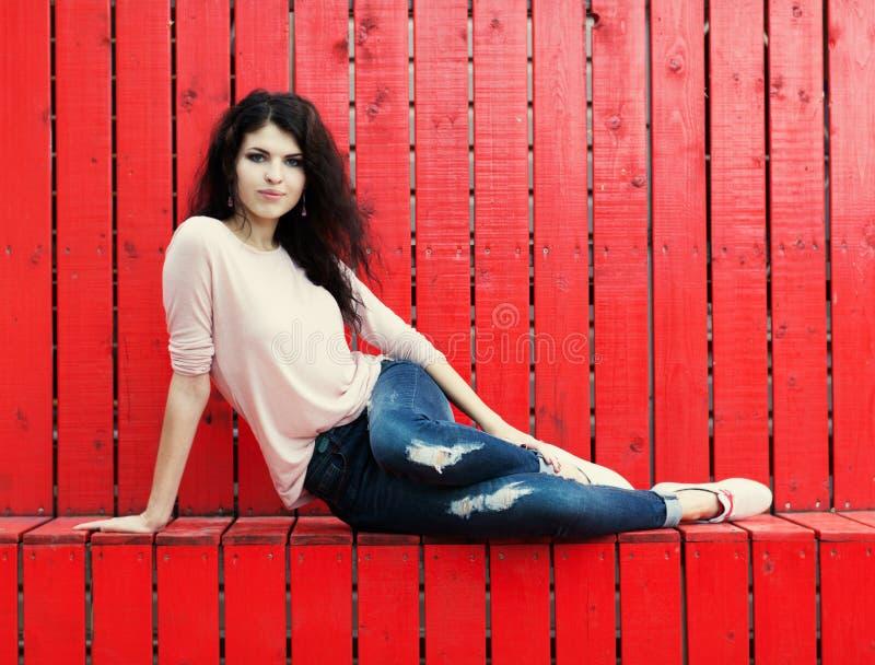 La bella ragazza con capelli lunghi castana in jeans si siede vicino alla parete delle plance di legno rosse fotografie stock libere da diritti