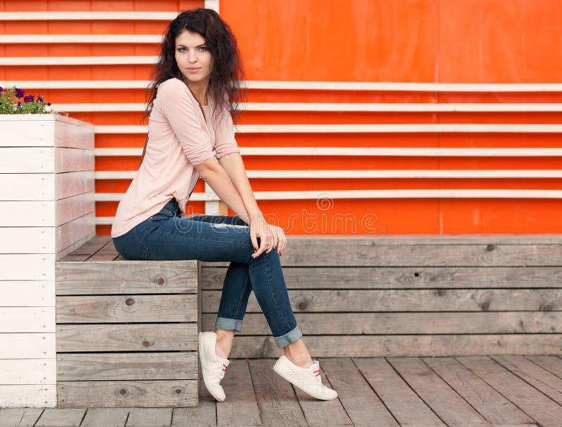 La bella ragazza con capelli lunghi castana in jeans si siede vicino alla parete di vecchie plance di legno bianche arancio immagini stock