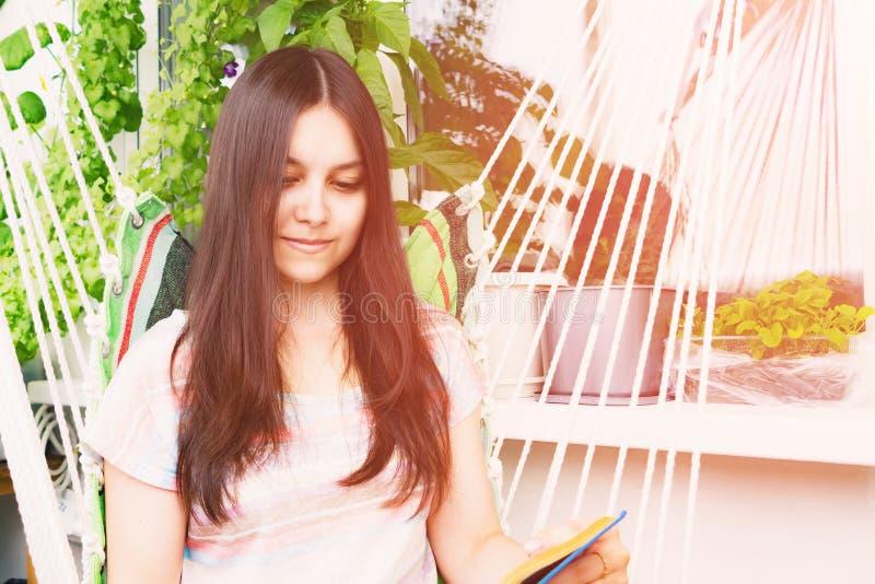 La bella ragazza con capelli scuri lunghi legge un libro che si siede in un'amaca sul balcone fotografia stock libera da diritti