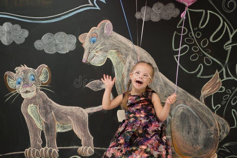 La bella ragazza con giù la sindrome del ` s celebra il suo compleanno fotografia stock