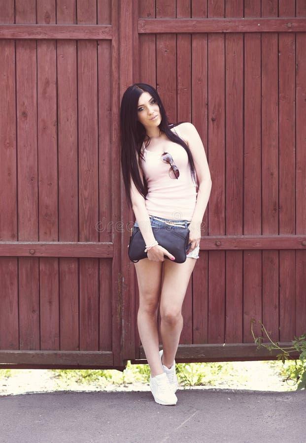 La bella ragazza con gli shorts di vetro e la blusa rosa sta davanti ad un recinto di legno, scarpe da tennis alla moda di modo fotografie stock