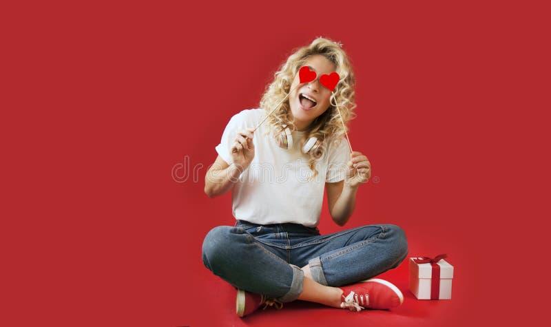 La bella ragazza con i cuori rossi e un regalo bianco con un arco si siede nella piena crescita un giorno dei backgroundValentine immagini stock