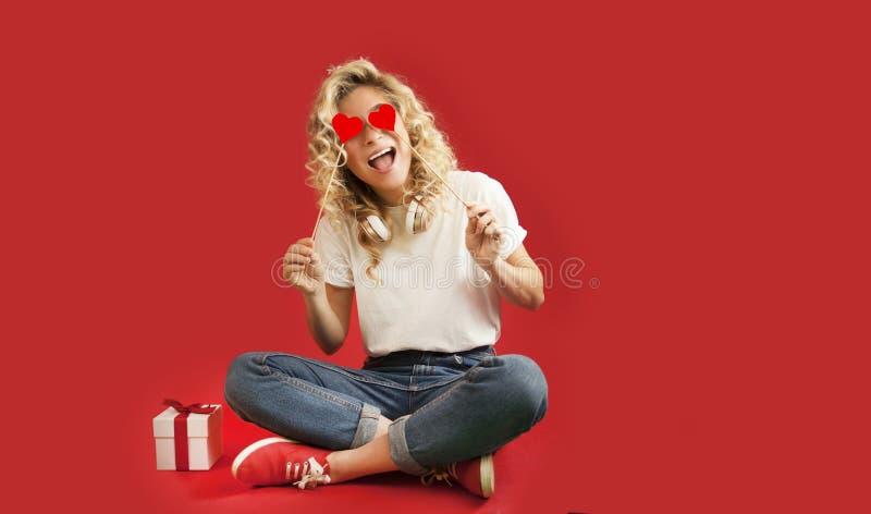 La bella ragazza con i cuori rossi e un regalo bianco con un arco si siede nella piena crescita un giorno dei backgroundValentine fotografia stock libera da diritti