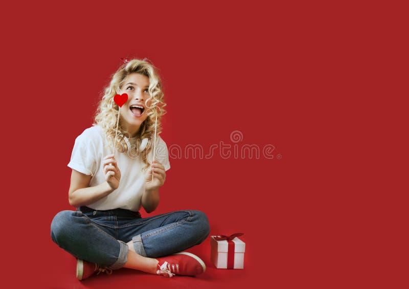 La bella ragazza con i cuori rossi e un regalo bianco con un arco si siede nella piena crescita un giorno dei backgroundValentine immagini stock libere da diritti