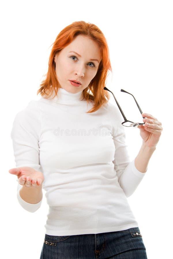 La bella ragazza con i vetri da portare dei capelli rossi comunica immagine stock