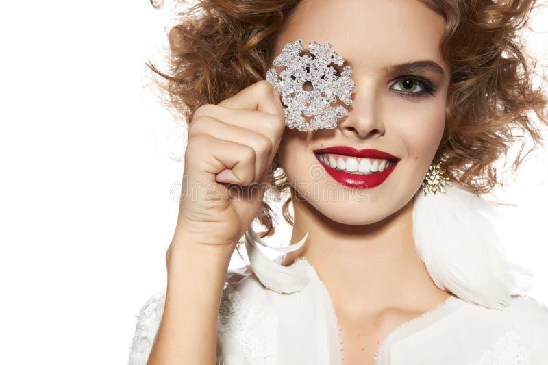 La bella ragazza con il sorriso di trucco di sera prende il fiocco di neve cristal immagini stock libere da diritti
