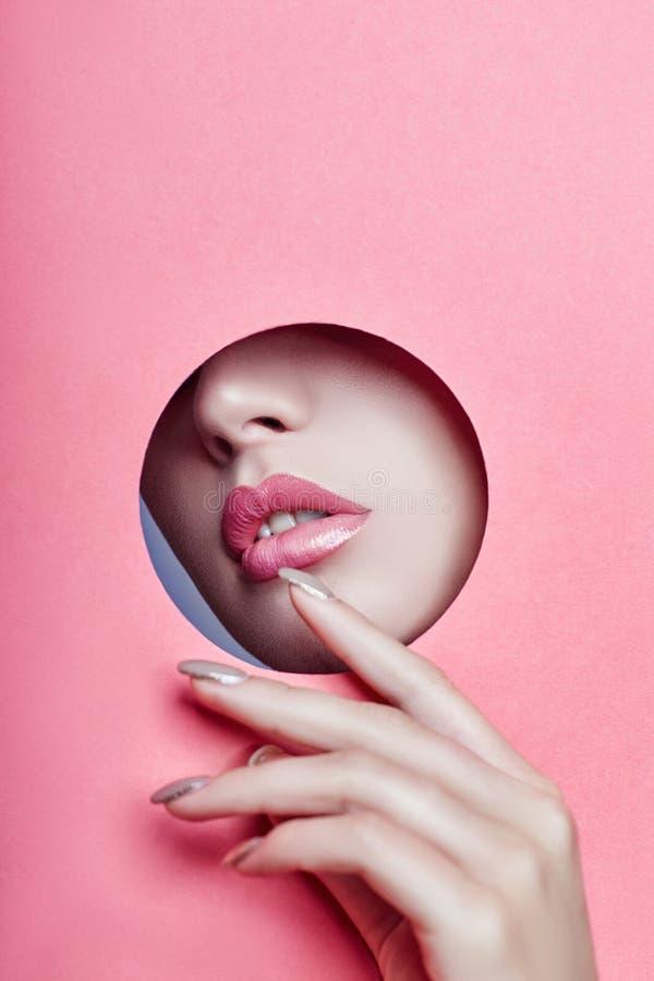 La bella ragazza con le labbra grassottelle rosa dà una occhiata a fuori attraverso un giro uff immagini stock libere da diritti