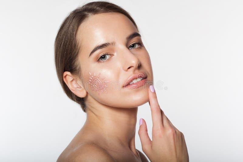 La bella ragazza con suncreen la crema su pelle immagini stock libere da diritti