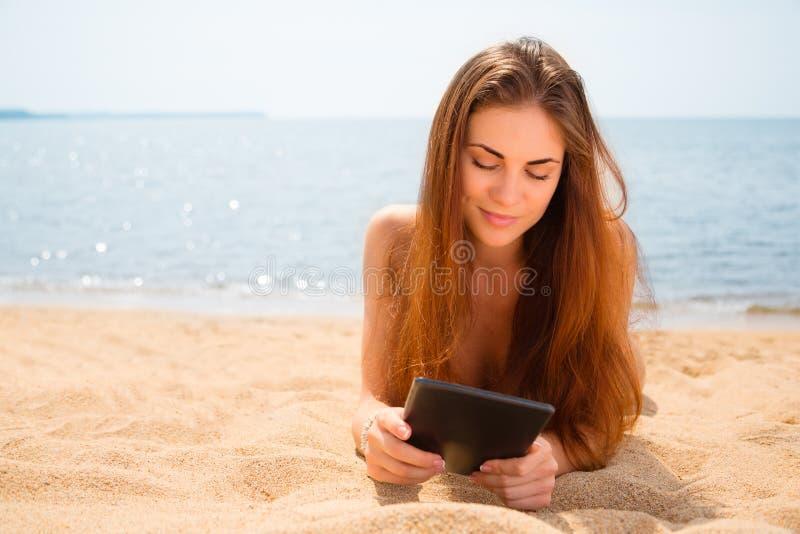 La bella ragazza con un PC della compressa sta trovandosi sulla spiaggia immagine stock libera da diritti