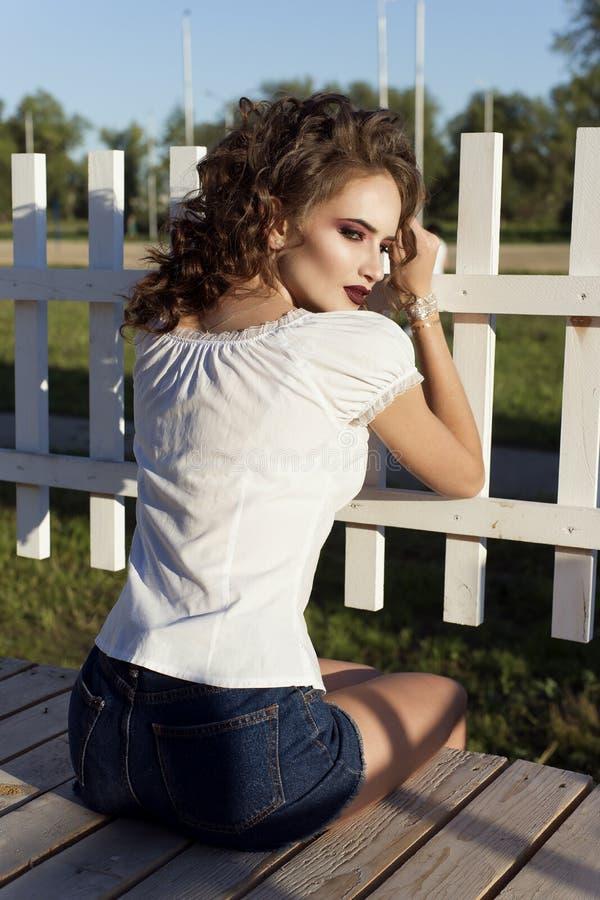 La bella ragazza contro lo sfondo di piccolo recinto bianco fotografia stock