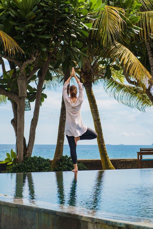 La bella ragazza dalla parte posteriore fa la pratica di yoga, meditazione, stante la posa nella località di soggiorno vicino all immagine stock