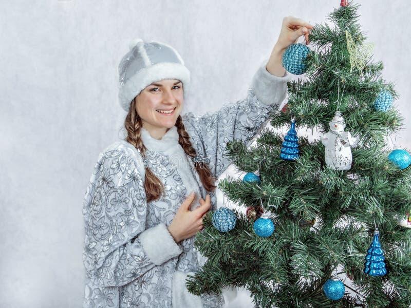 La bella ragazza della neve sta decorando un albero di Natale Nuovo anno e natale fotografie stock libere da diritti