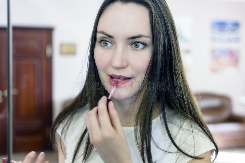 La bella ragazza dipinge le labbra nell'ufficio immagini stock libere da diritti